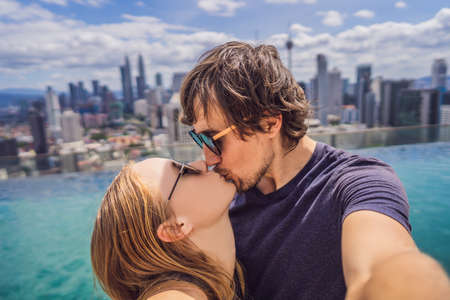 young happy and attractive playful couple taking selfie picture together at luxury urban hotel infinity pool and panoramic view of the city enjoying holidays honeymoon travel in diversity ethnicity and love Stockfoto