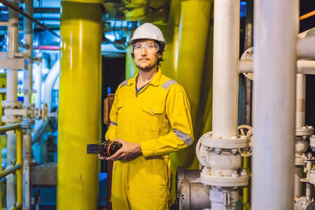 Young man in a yellow work uniform, glasses and helmet in industrial environment,oil Platform or liquefied gas plant