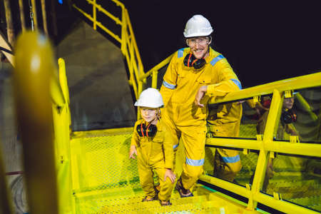 Young man and a little boy are both in a yellow work uniform, glasses, and helmet in an industrial environment, oil Platform or liquefied gas plant Imagens
