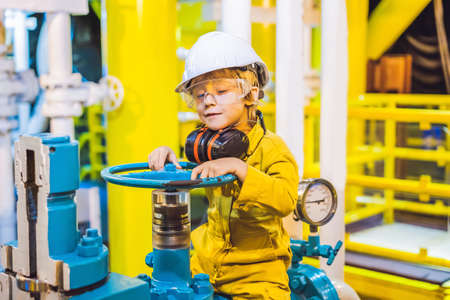 Boy operator recording operation of oil and gas process at oil and rig plant, offshore oil and gas industry, offshore oil and rig in the sea, operator monitor production process, routine daily record Imagens