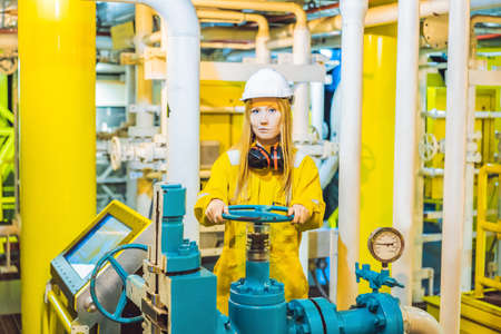 Junge Frau in gelber Arbeitsuniform, Brille und Helm in industrieller Umgebung, Ölplattform oder Flüssiggasanlage Standard-Bild