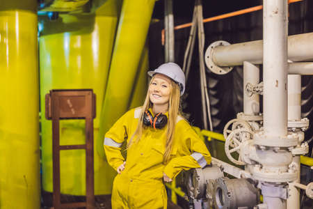 Young woman in a yellow work uniform, glasses and helmet in industrial environment,oil Platform or liquefied gas plant 版權商用圖片