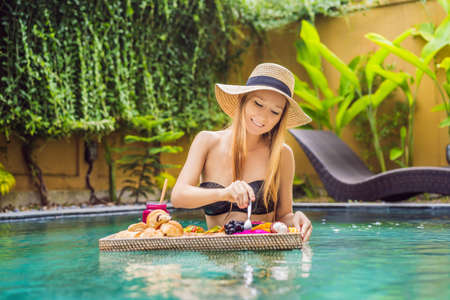 Breakfast tray in swimming pool, floating breakfast in luxury hotel. Girl relaxing in the pool drinking smoothies and eating fruit plate, smoothie bowl by the hotel pool. Exotic summer diet. Tropical beach lifestyle. Bali Trend