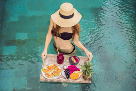 Breakfast tray in swimming pool, floating breakfast in luxury hotel. Girl relaxing in the pool drinking smoothies and eating fruit plate, smoothie bowl by the hotel pool. Exotic summer diet. Tropical beach lifestyle. Bali Trend Reklamní fotografie