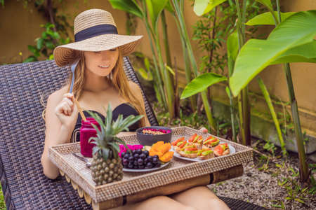 Young woman eating breakfast in a lounge chair on a tray with fruit, buns, avocado sandwiches, smoothie bowl by the pool. Summer healthy diet, vegan breakfast. Tasty vacation concept