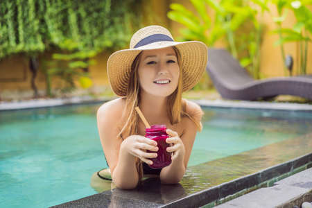 Young woman drinking Dragon fruit smoothies on the background of the pool. Fruit smoothie - healthy eating concept. Close up of detox smoothie with Dragon fruit
