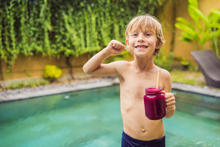 Cute boy holding a bottle of dragon fruit smoothie or juice is flexing his muscles and smiling