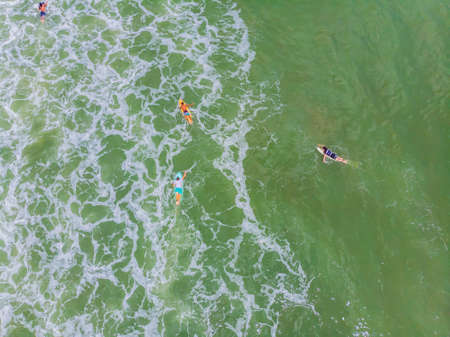 An aerial view of surfers waiting for a wave in the ocean on a clear day 版權商用圖片