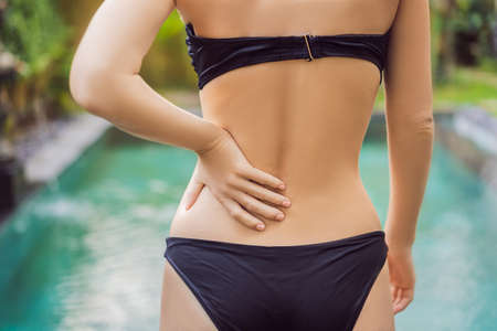 Womens back hurts against the backdrop of the pool. Pool helps with back pain