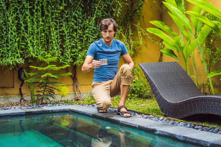 Pool worker checks the pool for safety. Measurement of chlorine and PH of a pool 版權商用圖片 - 122691651