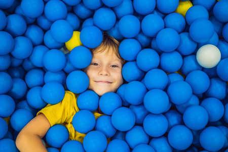 Niño jugando en la piscina de bolas. Juguetes coloridos para niños. Sala de juegos de jardín de infantes o preescolar. Niño pequeño en el patio interior de la guardería. Piscina de bolas para niños. Fiesta de cumpleaños para niños en edad preescolar activos