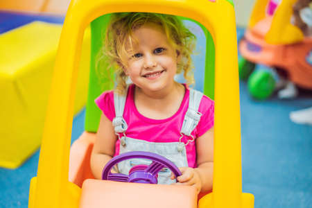 Little girl rides a toy colorful car Standard-Bild - 122691597