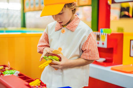 The boy plays in the toy kitchen, cooks a hamburger