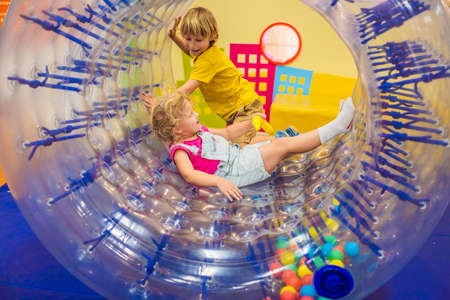 Cute little boy and girl playing in Zorb a rolling plastic cylinder ring with a hole in the middle, intdoor Фото со стока