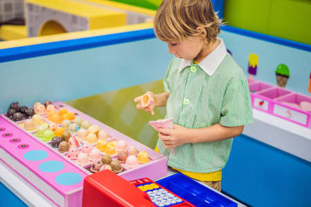 A boy plays in a toy kitchen, makes a toy ice cream
