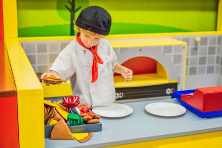 The boy plays in the toy kitchen, cooks a pizza