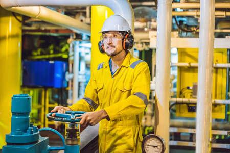 Junger Mann in gelber Arbeitsuniform, Brille und Helm in industrieller Umgebung, Ölplattform oder Flüssiggasanlage Standard-Bild