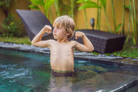 A boy shows his muscles after swimming Stock Photo