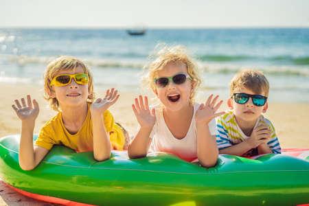 孩子们坐在一个充气床垫上,太阳镜对着海洋,玩得开心
