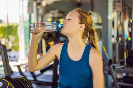 Young athletic woman drinking water in gym