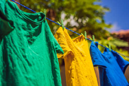 Multicolor shirts on clothesline in sunny day Archivio Fotografico