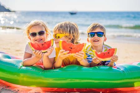 Kinderen eten watermeloen op het strand in zonnebril Stockfoto