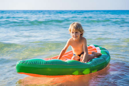 The boy swims in the sea on an inflatable mattress
