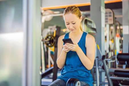 Young woman using phone while training at the gym. Woman sitting on exercising machine holding mobile phone Imagens