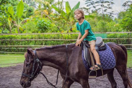 Boy horseback riding, performing exercises on horseback Reklamní fotografie