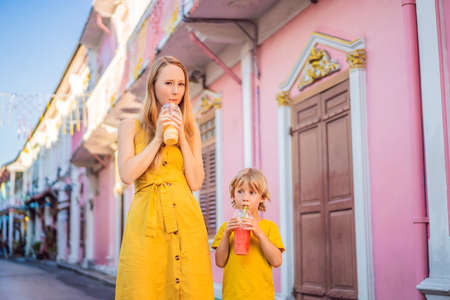 Mom and son tourists on the Street in the Portugese style Romani in Phuket Town. Also called Chinatown or the old town. Traveling with kids concept Stock Photo