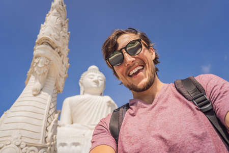 Man tourist on background of Big Buddha statue Was built on a high hilltop of Phuket Thailand Can be seen from a distance Stock Photo