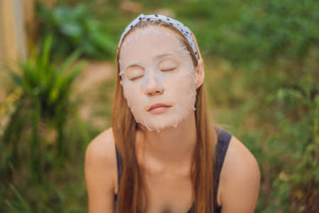 Face care and beauty treatments. Woman with a sheet moisturizing mask on her face 写真素材 - 124752922