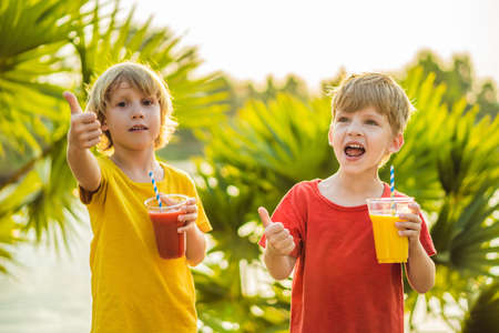 Two boys drink healthy smoothies against the backdrop of palm trees.