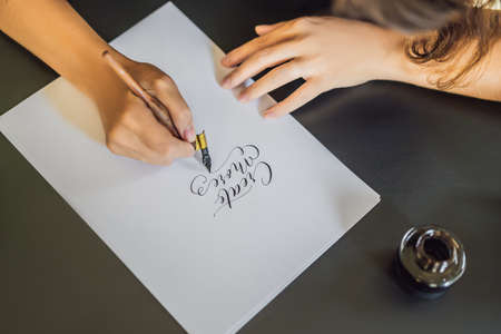 Creat more. Calligrapher Young Woman writes phrase on white paper. Inscribing ornamental decorated letters. Calligraphy, graphic design, lettering, handwriting, creation concept Stockfoto