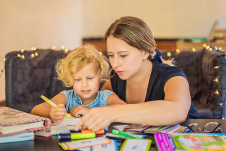 A teacher, a tutor for home schooling and a teacher at the table. Or mom and daughter. Homeschooling