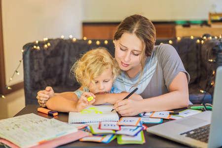 Un enseignant, un tuteur pour l'enseignement à domicile et un enseignant à table. Ou maman et fille. Enseignement à domicile