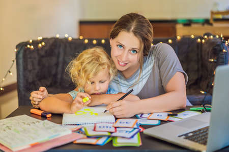 A teacher, a tutor for home schooling and a teacher at the table. Or mom and daughter. Homeschooling Stock Photo