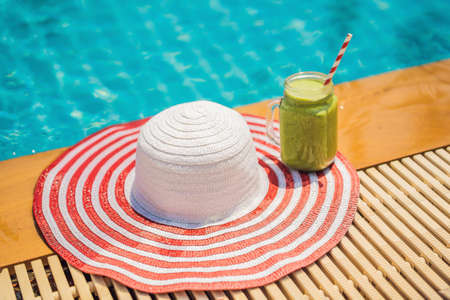 Green smoothies of spinach and banana on the background of the pool. Healthy food, healthy smoothies