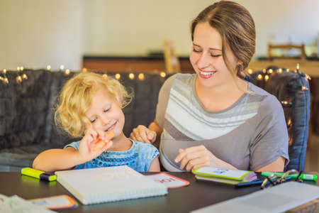 A teacher, a tutor for home schooling and a teacher at the table. Or mom and daughter. Homeschooling Фото со стока