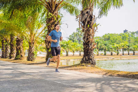 Runner athlete running at tropical park. man fitness sunrise jogging workout wellness concept 版權商用圖片