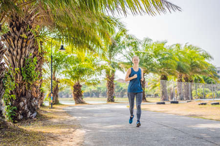 Runner athlete running at tropical park. woman fitness sunrise jogging workout wellness concept 版權商用圖片 - 124753090