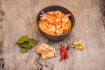 Prawn and lemon grass soup with mushrooms,Tom Yam Kung ,thai food in wooden background, top view Stock Photo - 124754939