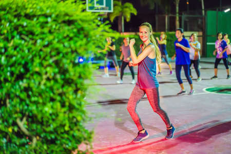 Young woman on a group workout on the basketball court in the evening Stock Photo