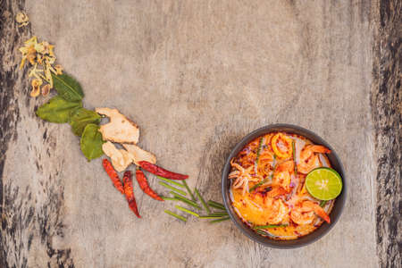Prawn and lemon grass soup with mushrooms,Tom Yam Kung ,thai food in wooden background, top view Banco de Imagens