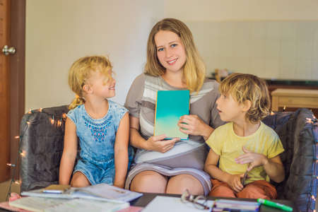Teacher, tutor for home schooling Boy and girl at the table. Or mother, daughter and son. Homeschooling Banco de Imagens