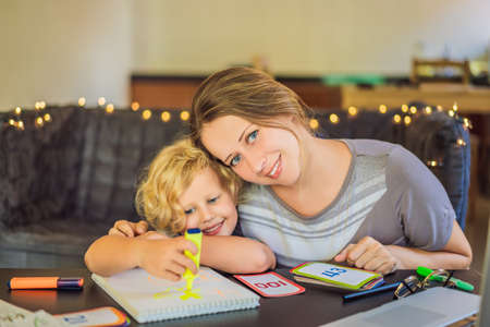 A teacher, a tutor for home schooling and a teacher at the table. Or mom and daughter. Homeschooling Banco de Imagens