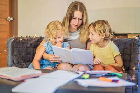 Teacher, tutor for home schooling Boy and girl at the table. Or mother, daughter and son. Homeschooling Фото со стока