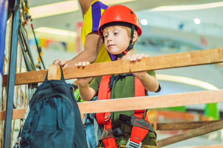 Adorable little boy enjoying his time in climbing adventure park in the mall Archivio Fotografico - 125058066