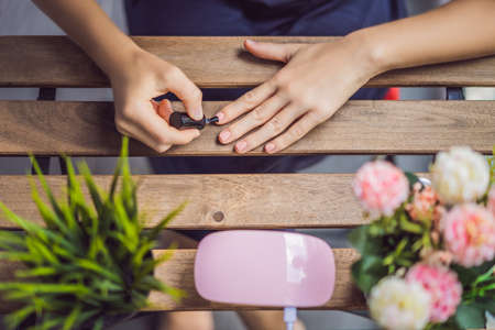 Young woman makes manicure with gel polish and UV lamp in pink shades.