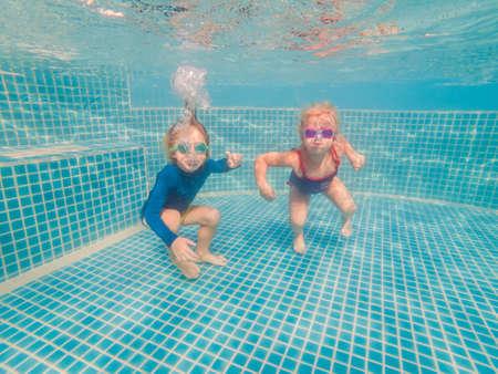 孩子们在暑假的游泳池玩水下的乐趣